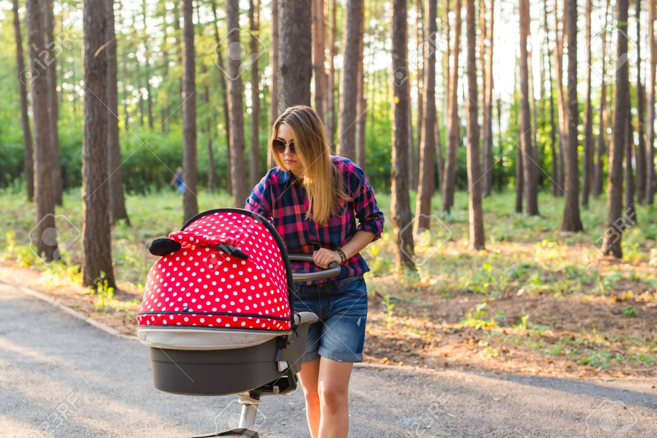 b5de5d066b39 Young Mother Walking And Pushing A Stroller In The Park. Woman ...
