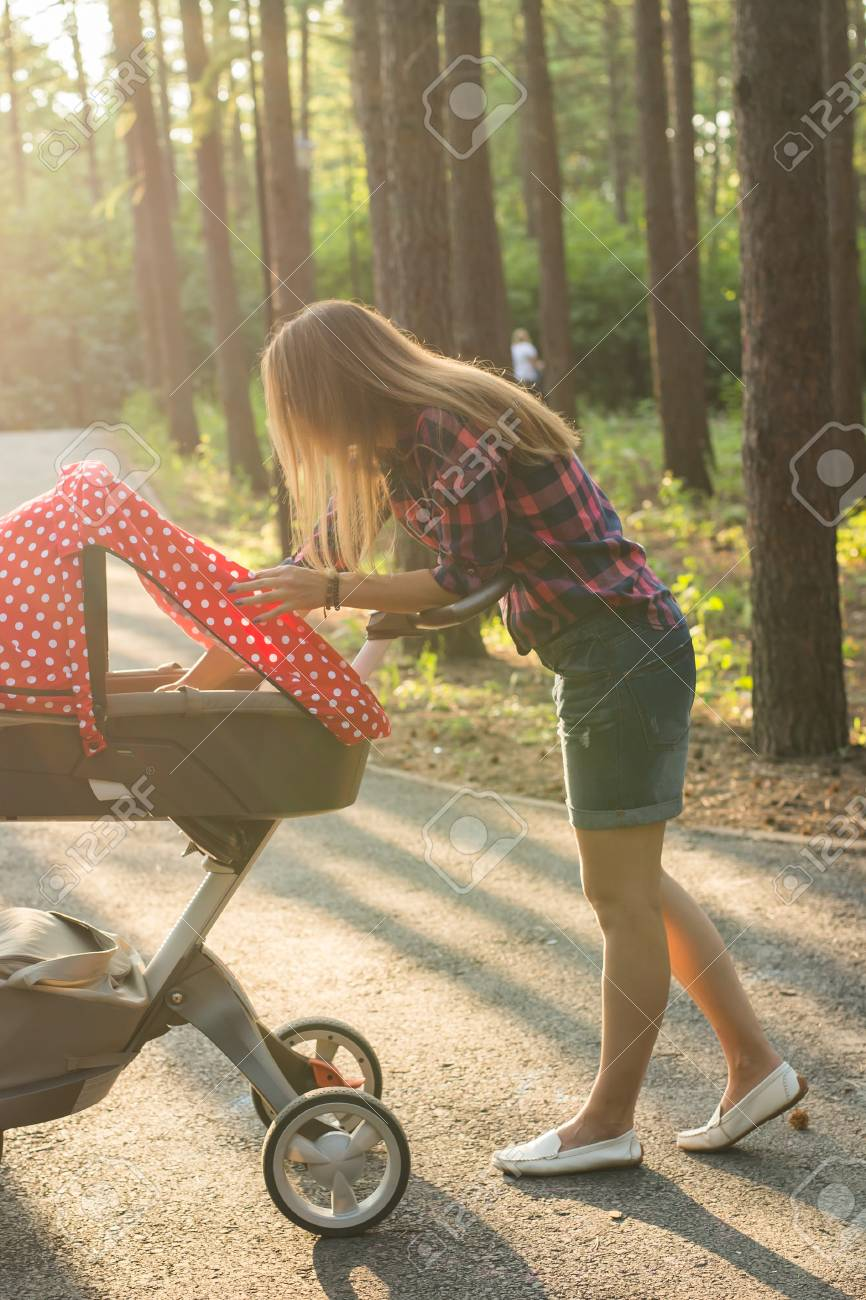 19588397bdbb Young Mother Walking And Pushing A Stroller In The Park. Mother ...