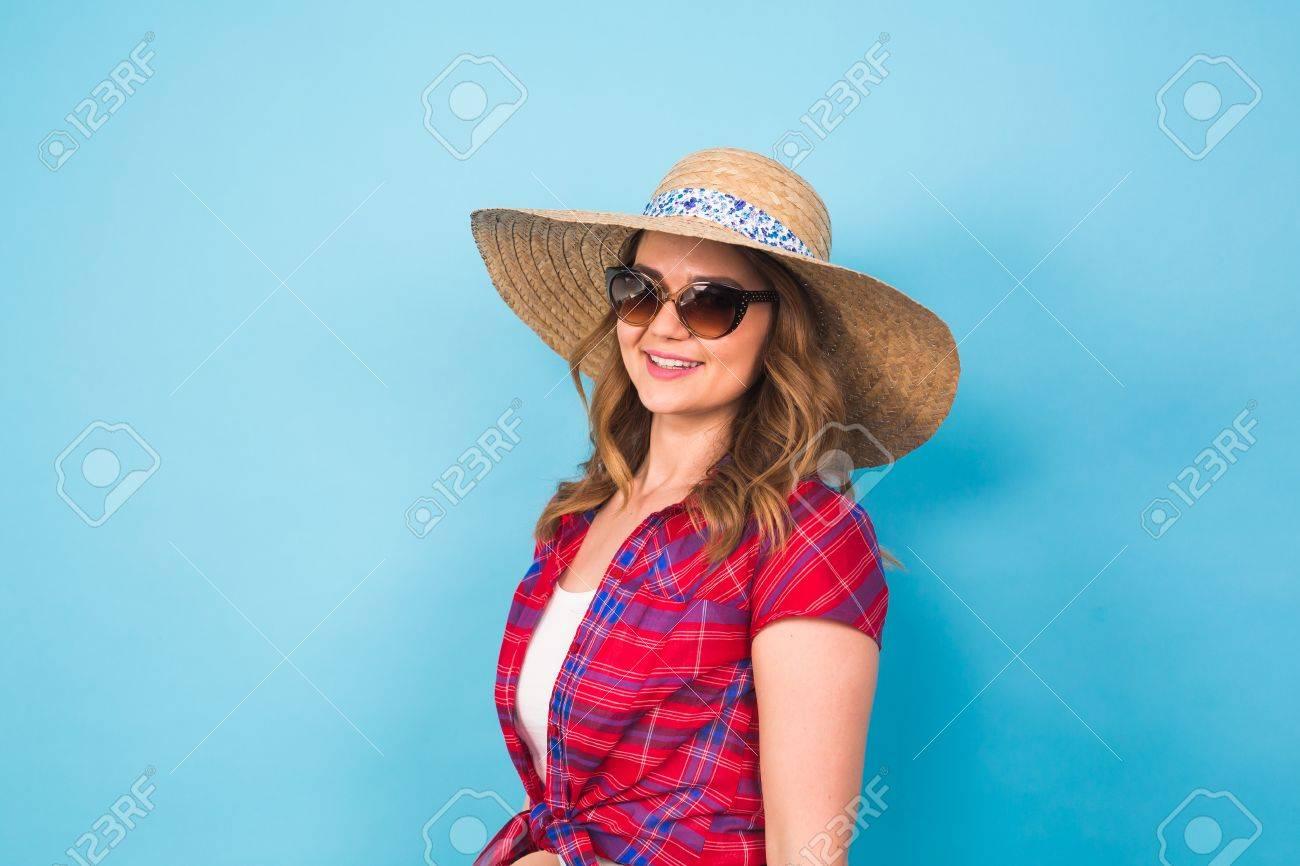 01d4caa8a Foto de archivo - Hermosa mujer joven lleva en vestido de verano y sombrero  de paja se ríe sobre fondo azul con copia espacio