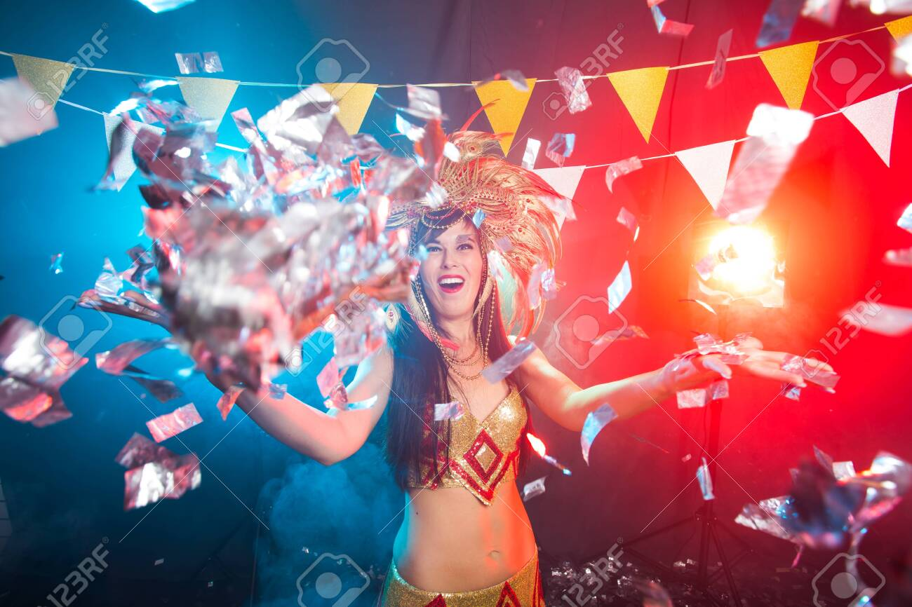 Cabaret, dancer and holidays concept - Cute young girl in bright colorful carnival costume on dark background - 129556960