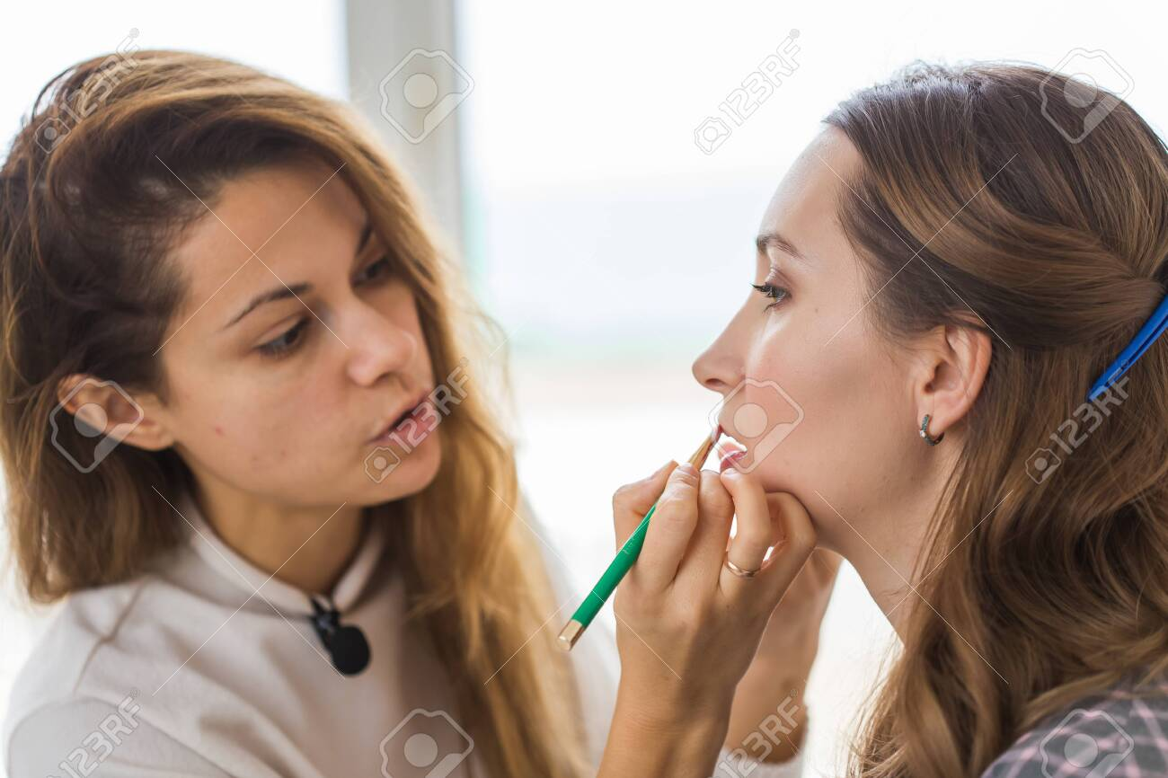 Beauty and cosmetics concept - Makeup artist doing professional make up of young woman - 143572830