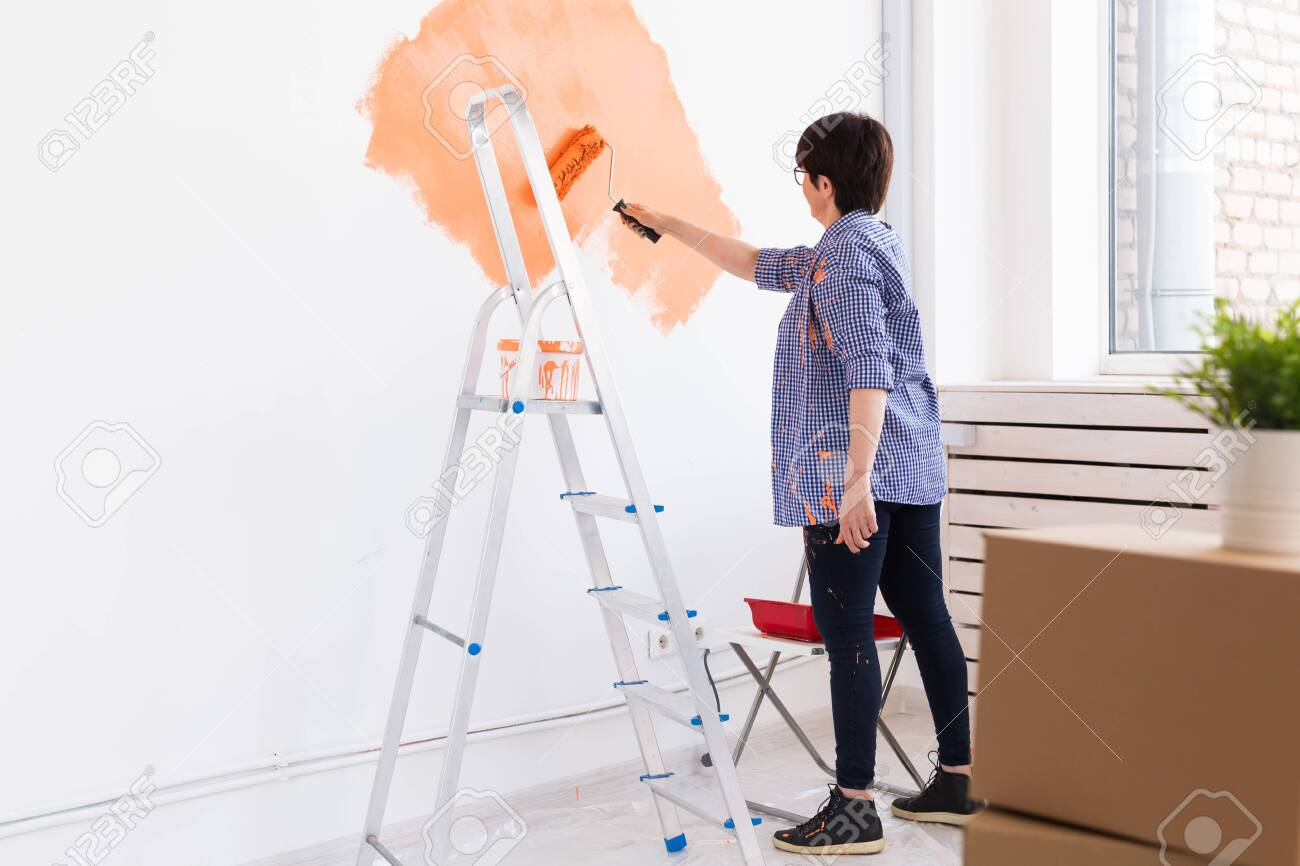 Happy middle-aged woman painting wall in her new apartment. Renovation, redecoration and repair concept. - 153679101