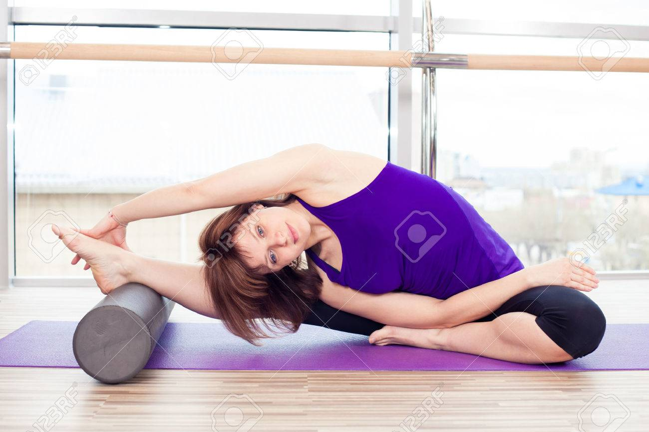 fitness, sport, training and lifestyle concept - woman doing pilates on the floor with foam roller - 40069260