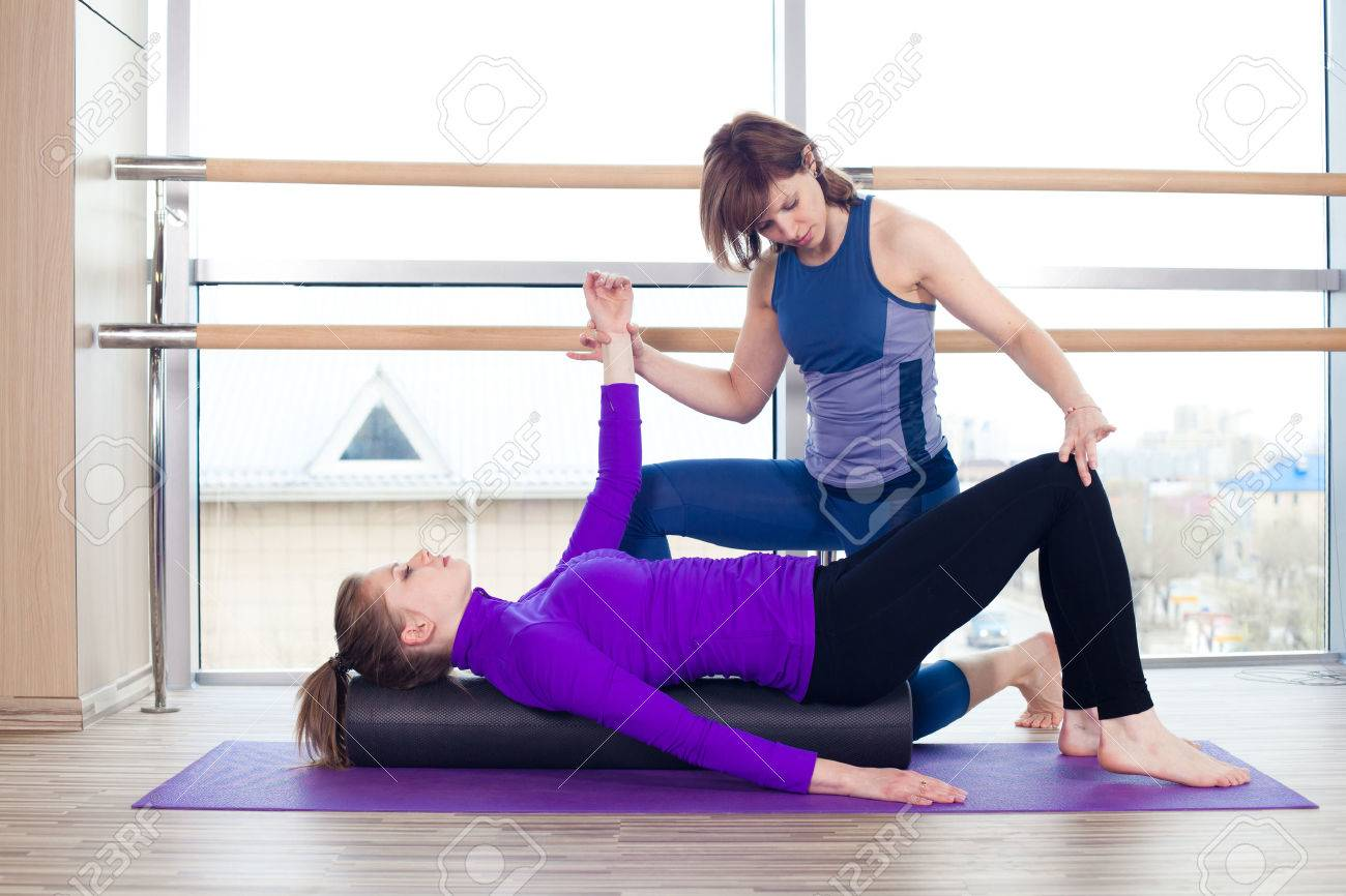 Aerobics Pilates personal trainer helping women group in a gym class - 40069278