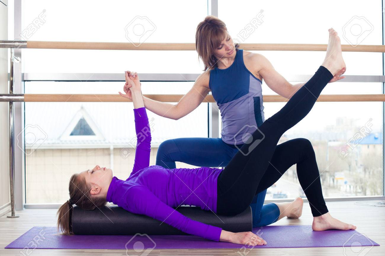 Aerobics Pilates personal trainer helping women group in a gym class - 40069279