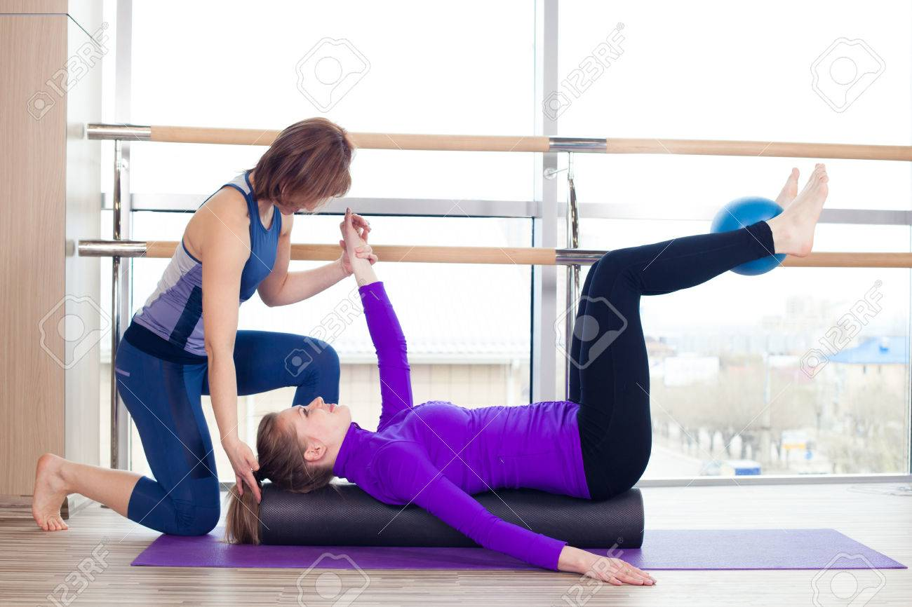 Aerobics Pilates personal trainer helping women group in a gym class - 40069288