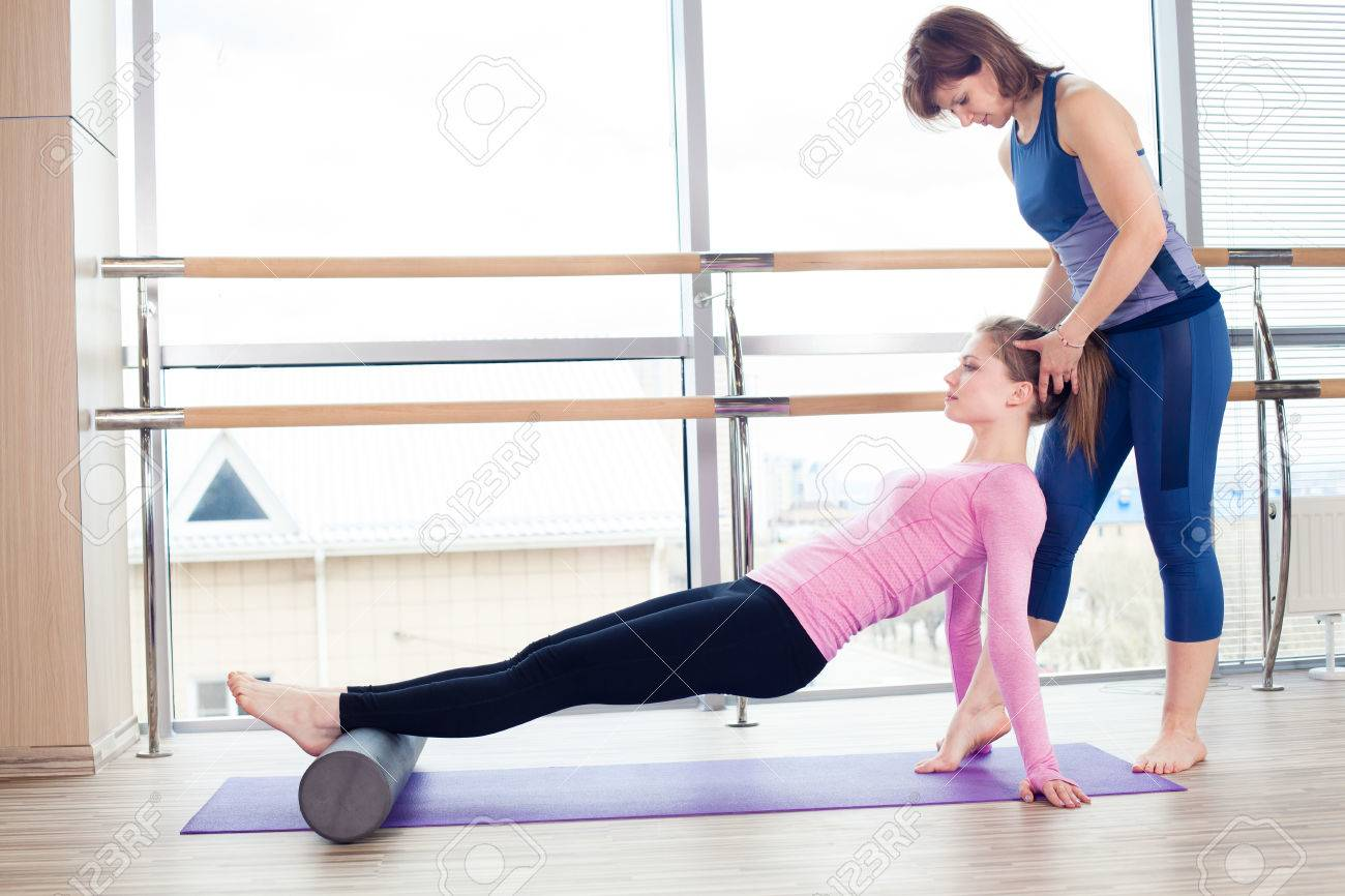 Aerobics Pilates personal trainer helping women group in a gym class - 40069286