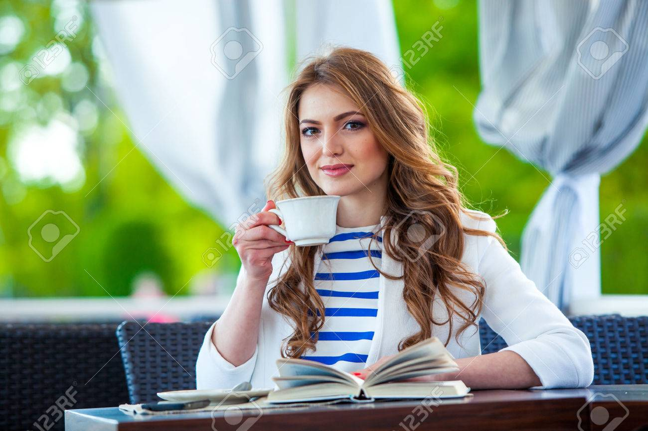 beautiful young girl in outdoor cafe reading a book and drinking coffee. phone. student. business woman - 40631496