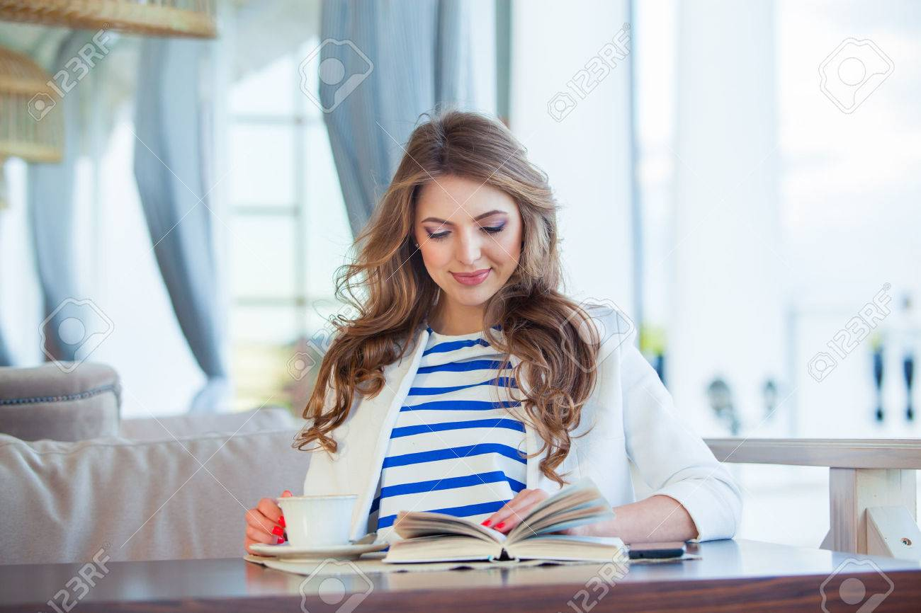 beautiful young girl in outdoor cafe reading a book and drinking coffee. phone. student. business woman - 40614580