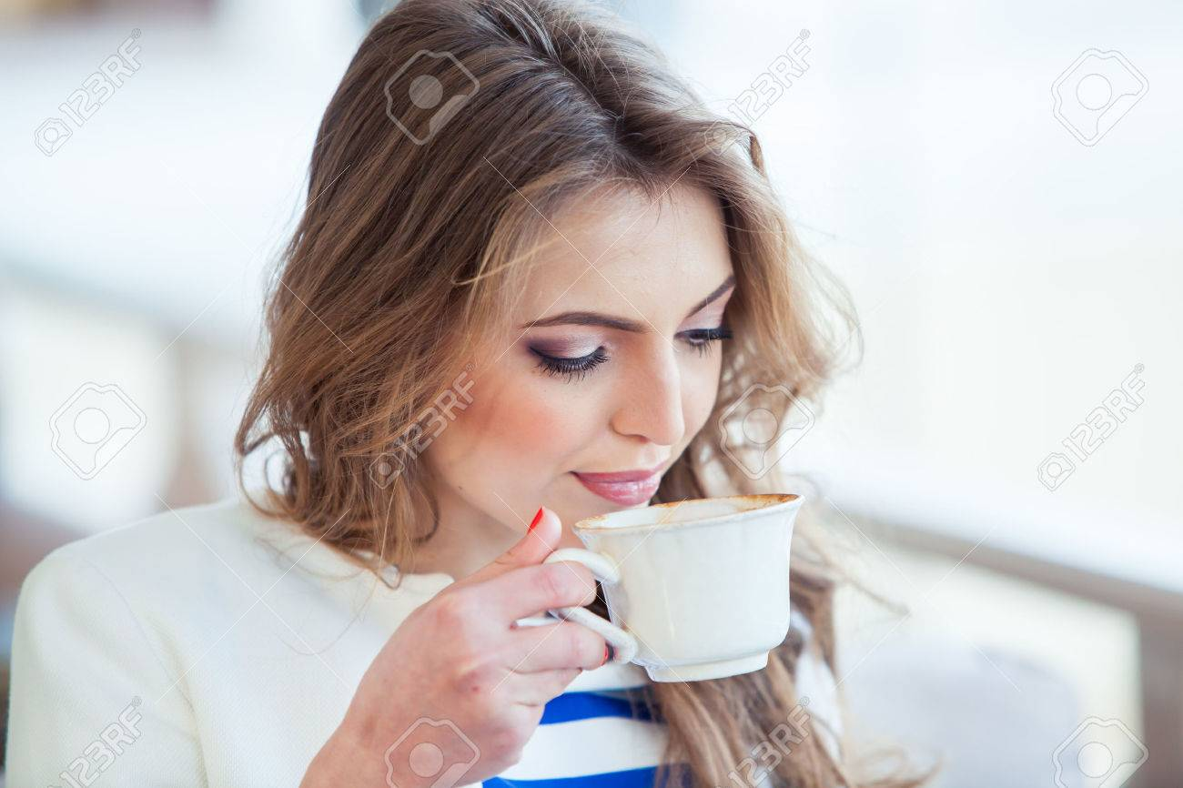 beautiful young girl in outdoor cafe reading a book and drinking coffee. phone. student. business woman - 40614774