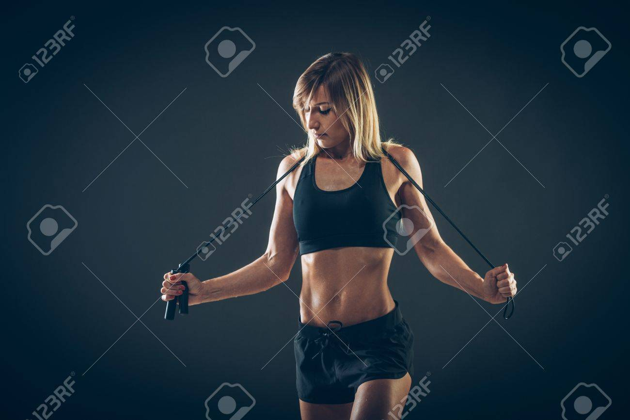Sport, activity. Cute woman with skipping rope. Muscular woman black background. - 43576345