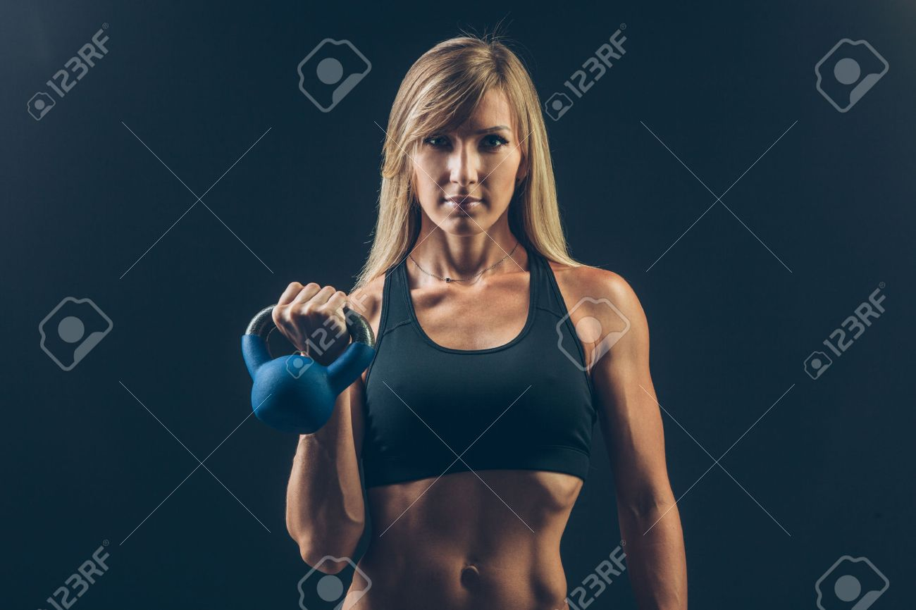 Fitness woman exercising crossfit holding kettlebell strength training biceps. Beautiful sweaty fitness instructor on blackoard background looking intense at camera. Asian Caucasian female model. - 43578001
