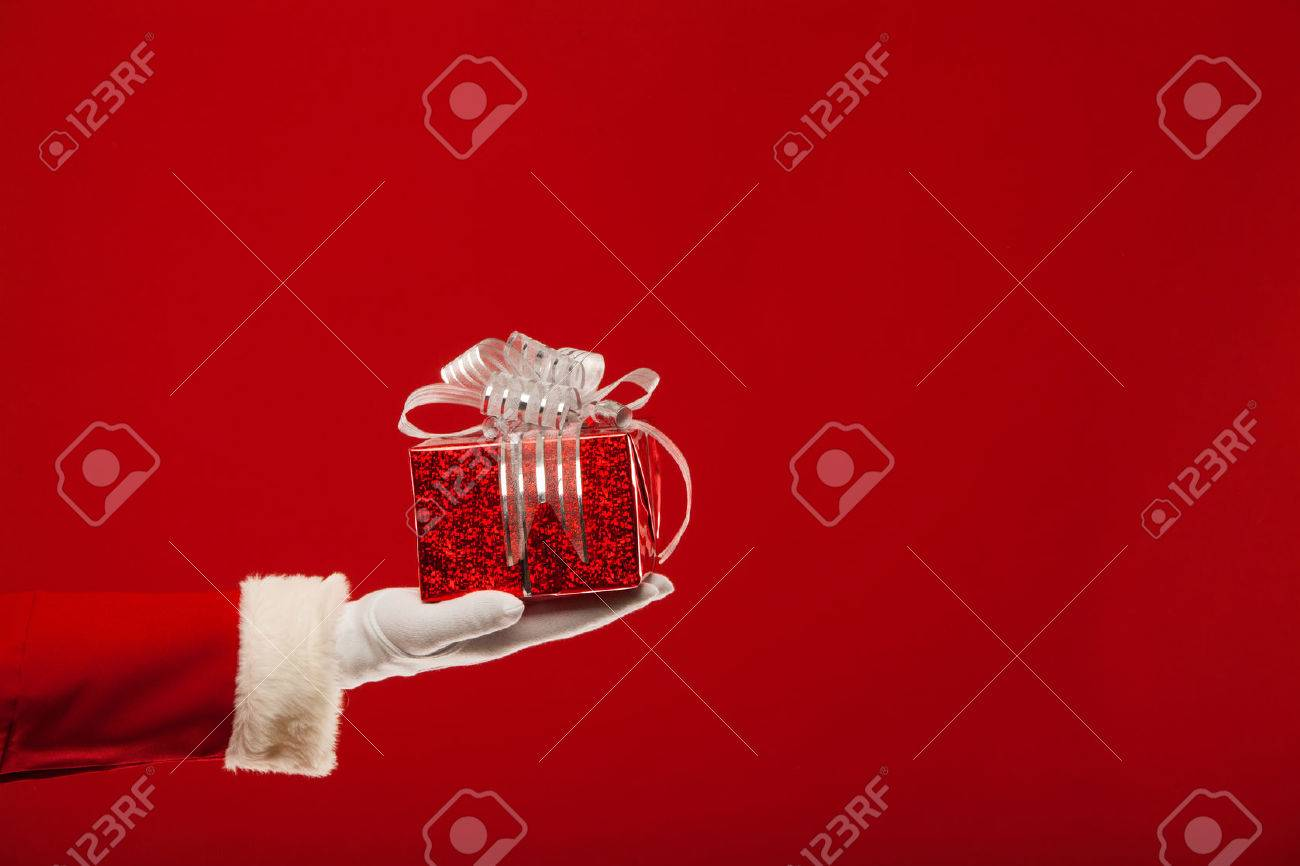 Photo of Santa Claus gloved hand with red giftbox, on a red background - 46517174