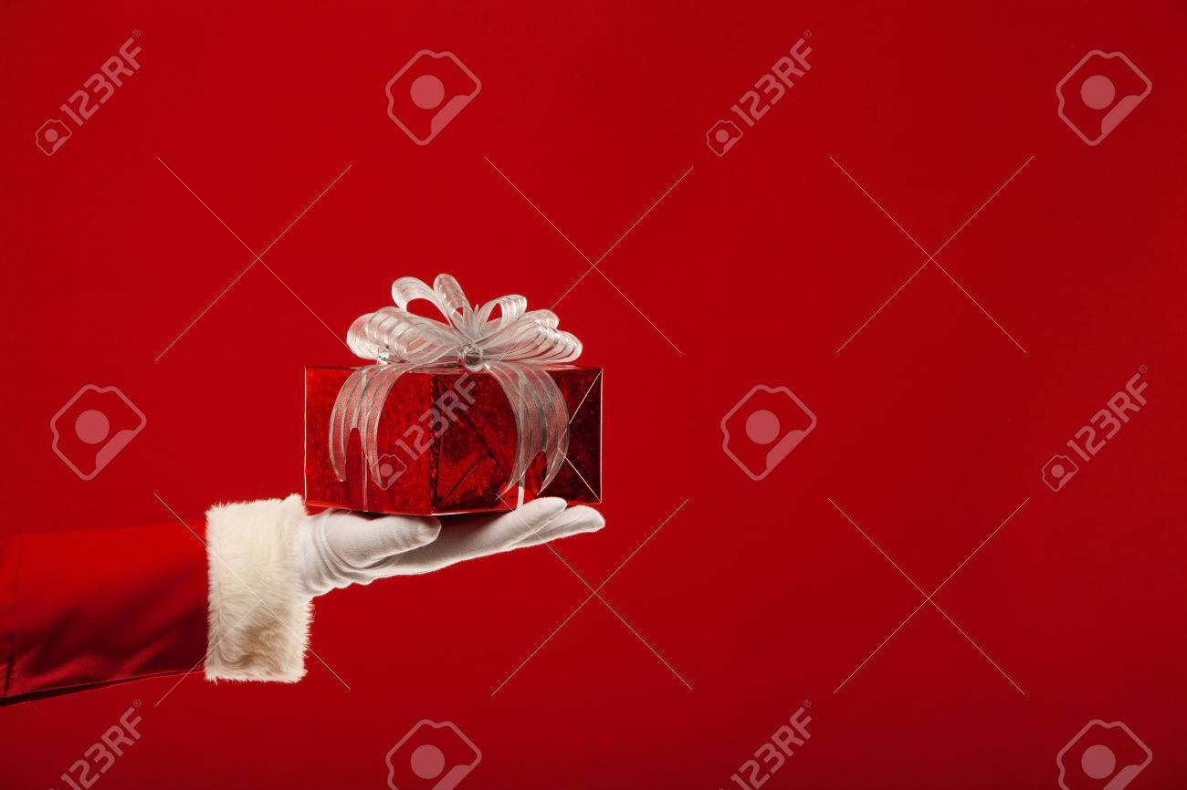 Photo of Santa hand with red giftbox, on a red background - 46517176