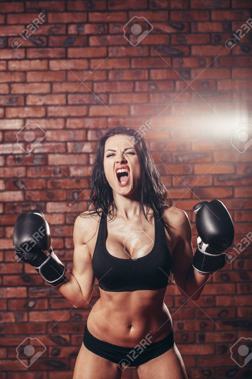 Young girl with boxing gloves, on the background wall of red brick - 47221564