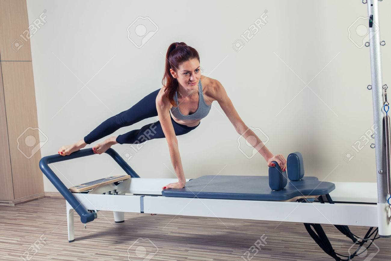 Pilates reformer workout exercises woman brunette at gym indoor. - 47852778