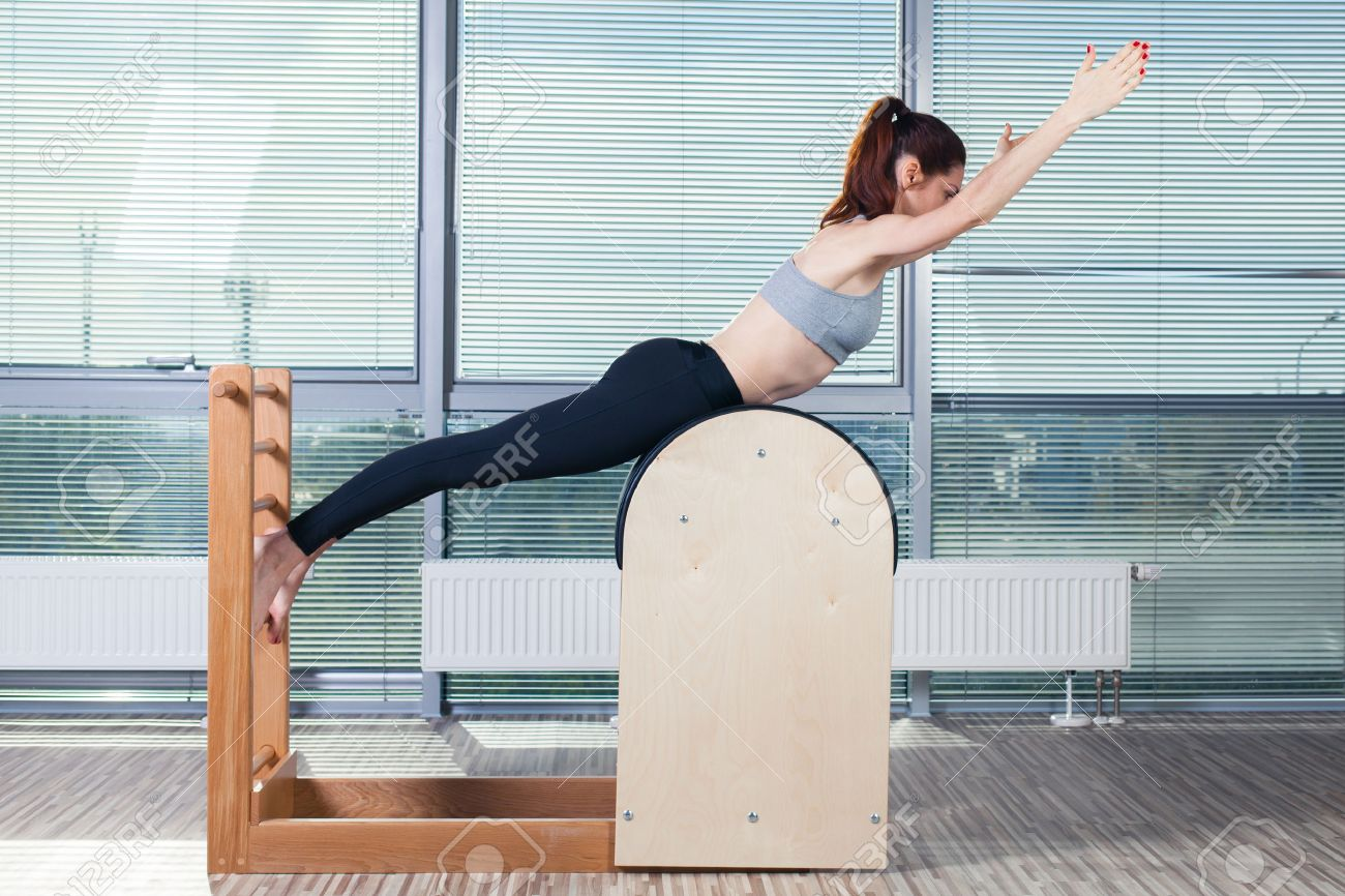 Pilates, fitness, sport, training and people concept - smiling woman doing exercises on ladder barrel. - 47935424