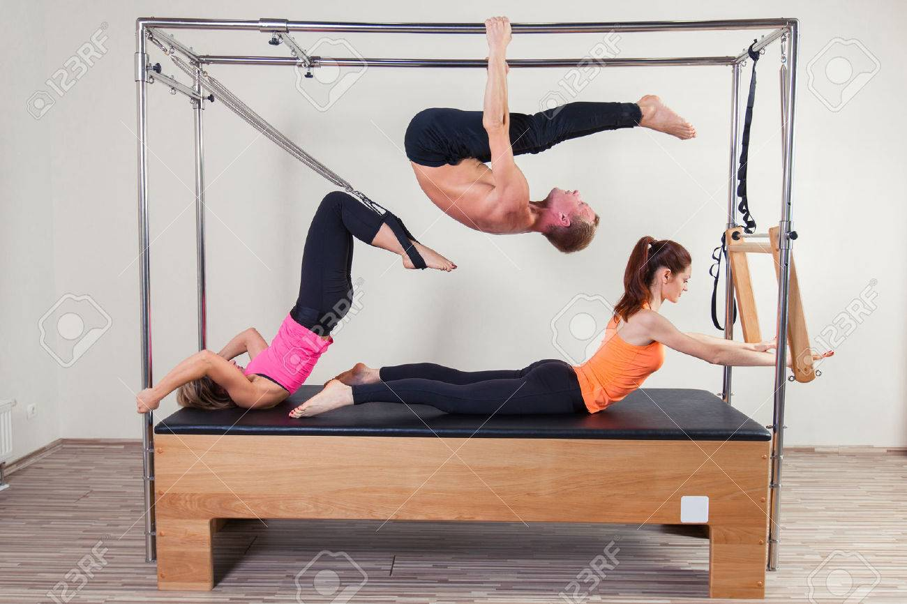 Pilates aerobic instructor a group of three people in cadillac fitness exercise. - 48284247