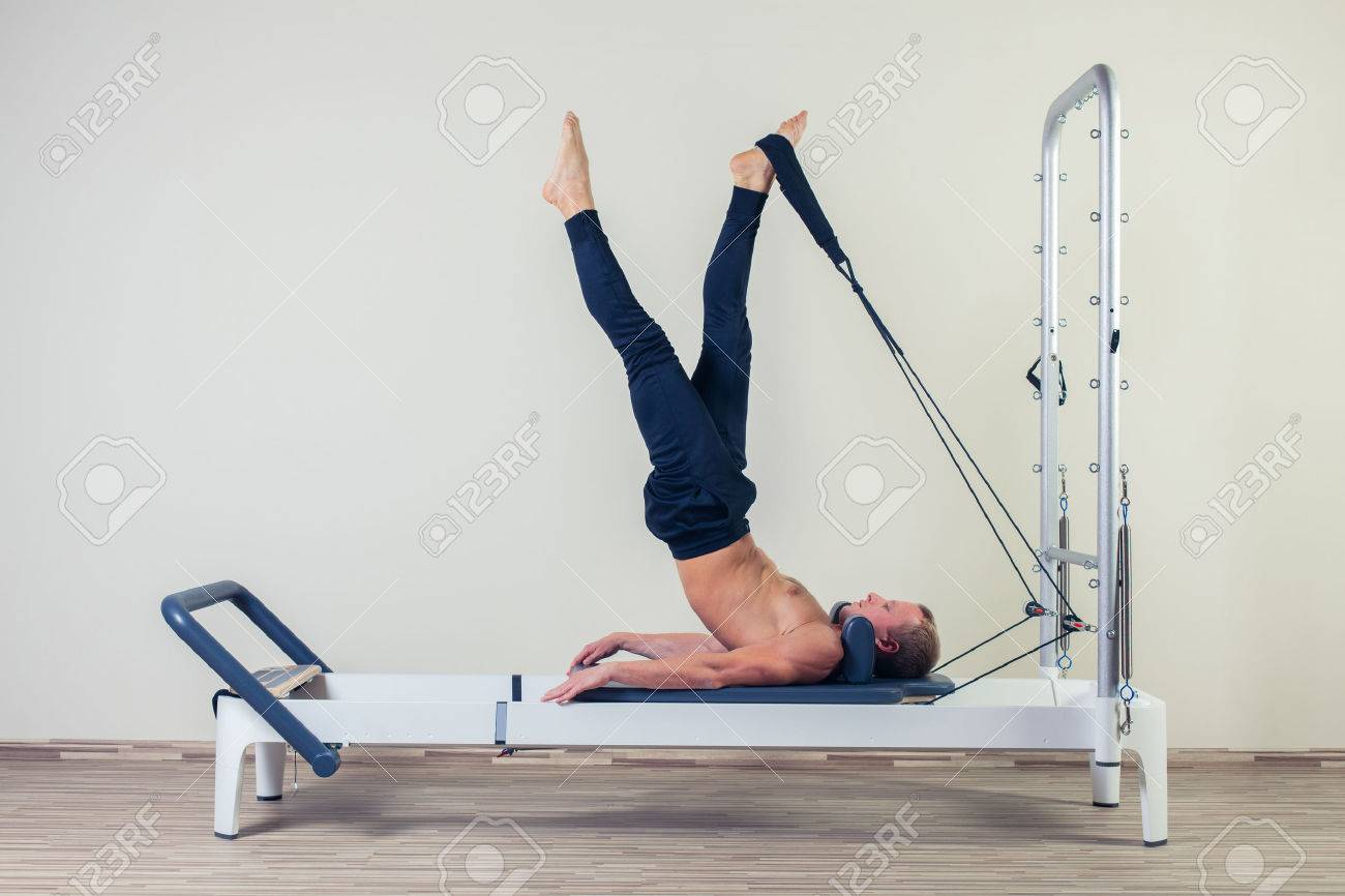 Pilates reformer workout exercises man at gym indoor. - 48284283