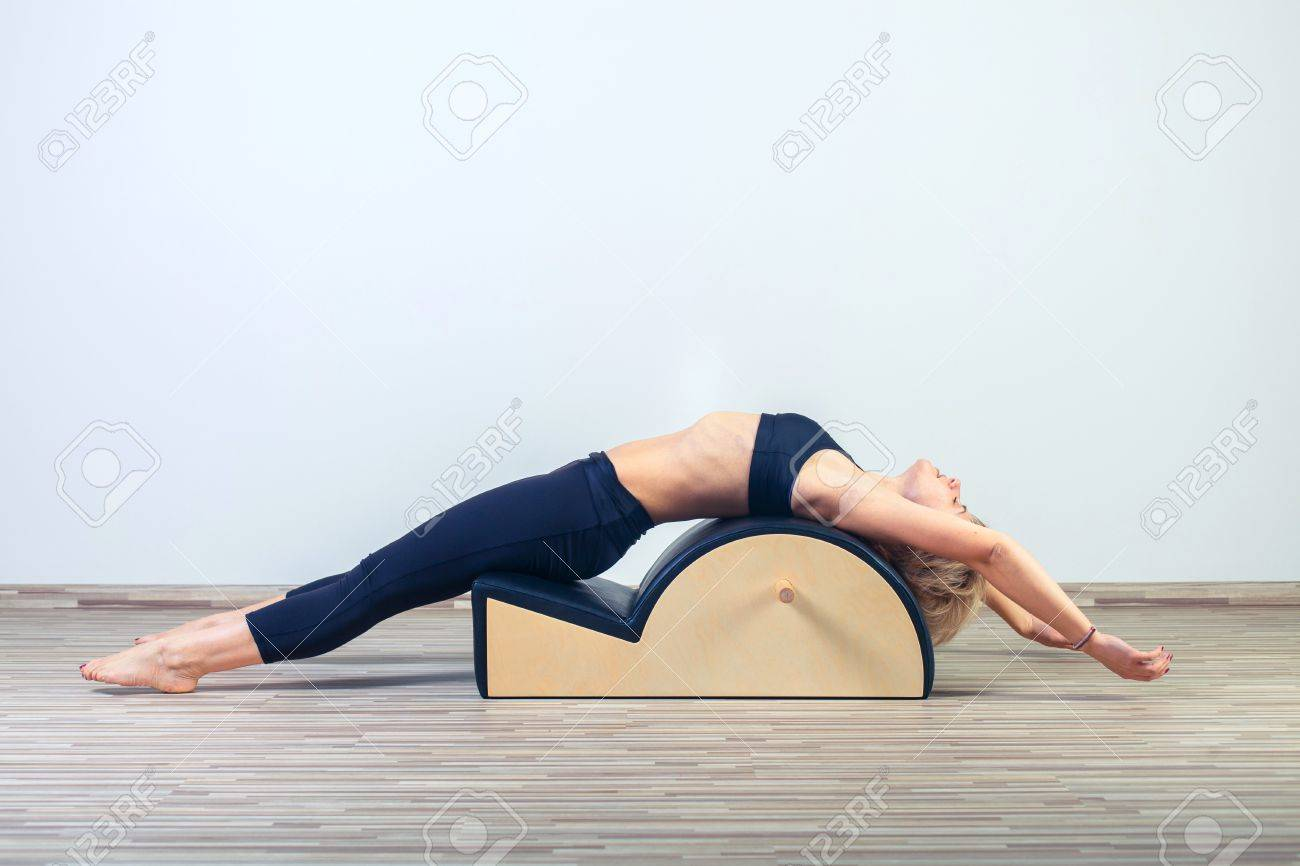 Pilates, fitness, sport, training and people concept - woman doing exercises on small barrel. - 48806382