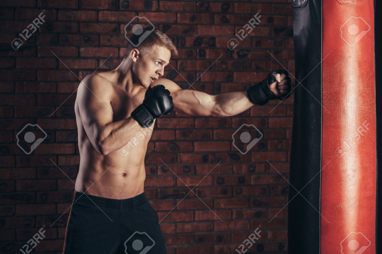 Boxer training on a punching bag in the gym - 51937097