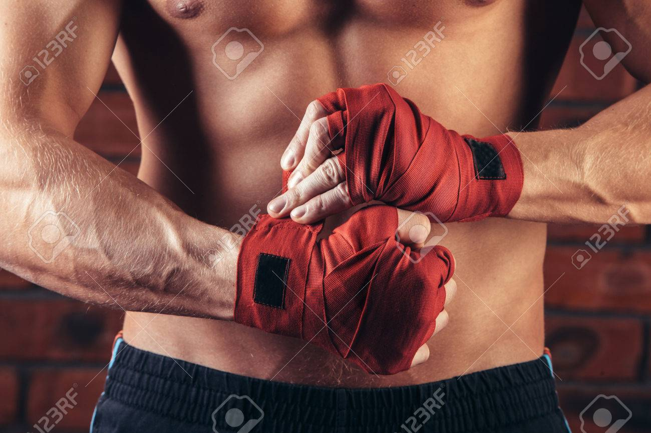 Muscular Fighter With Red Bandages against the background of a brick wall. - 53436562
