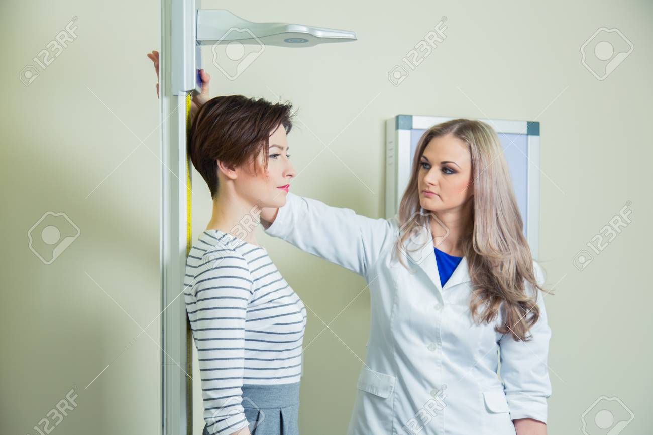 Doctor measures growth woman in medical office. - 56567494
