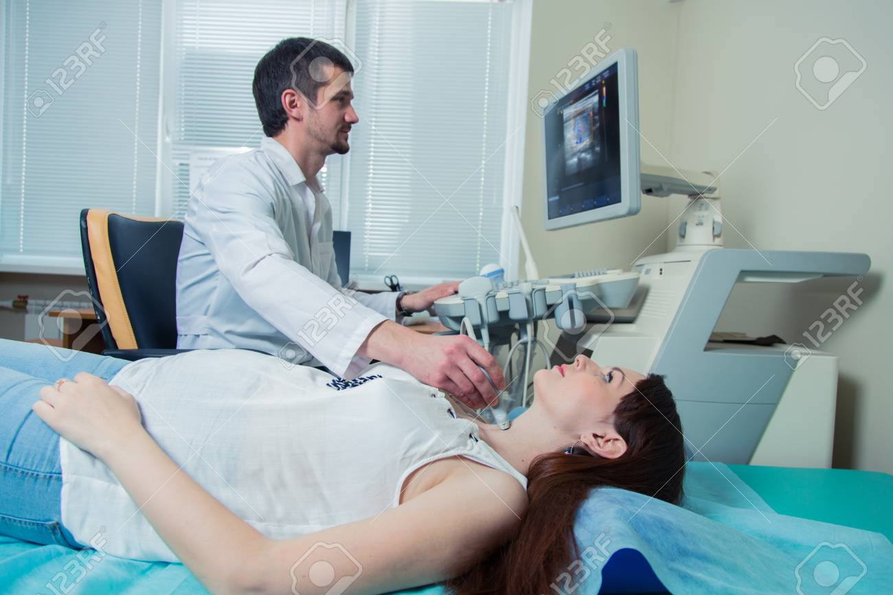 woman getting ultrasound of a thyroid from doctor. - 56567595