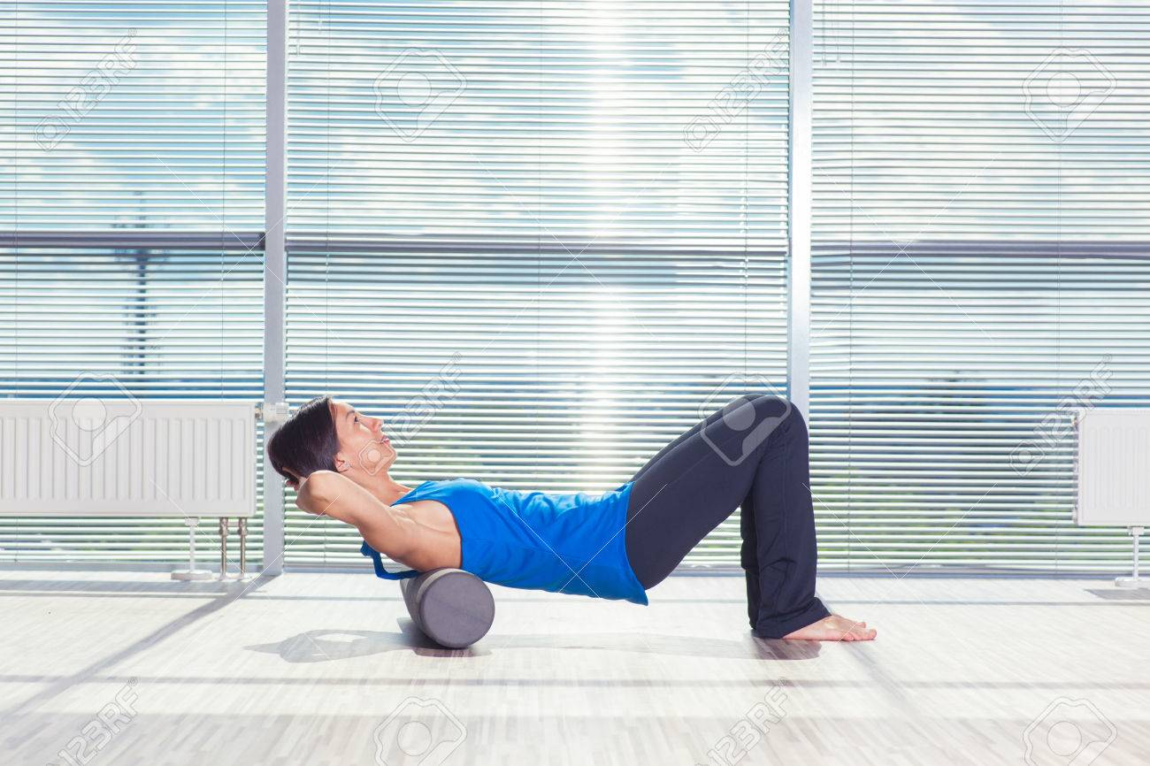 fitness, sport, training and lifestyle concept - woman doing pilates on the floor with foam roller. - 60759629