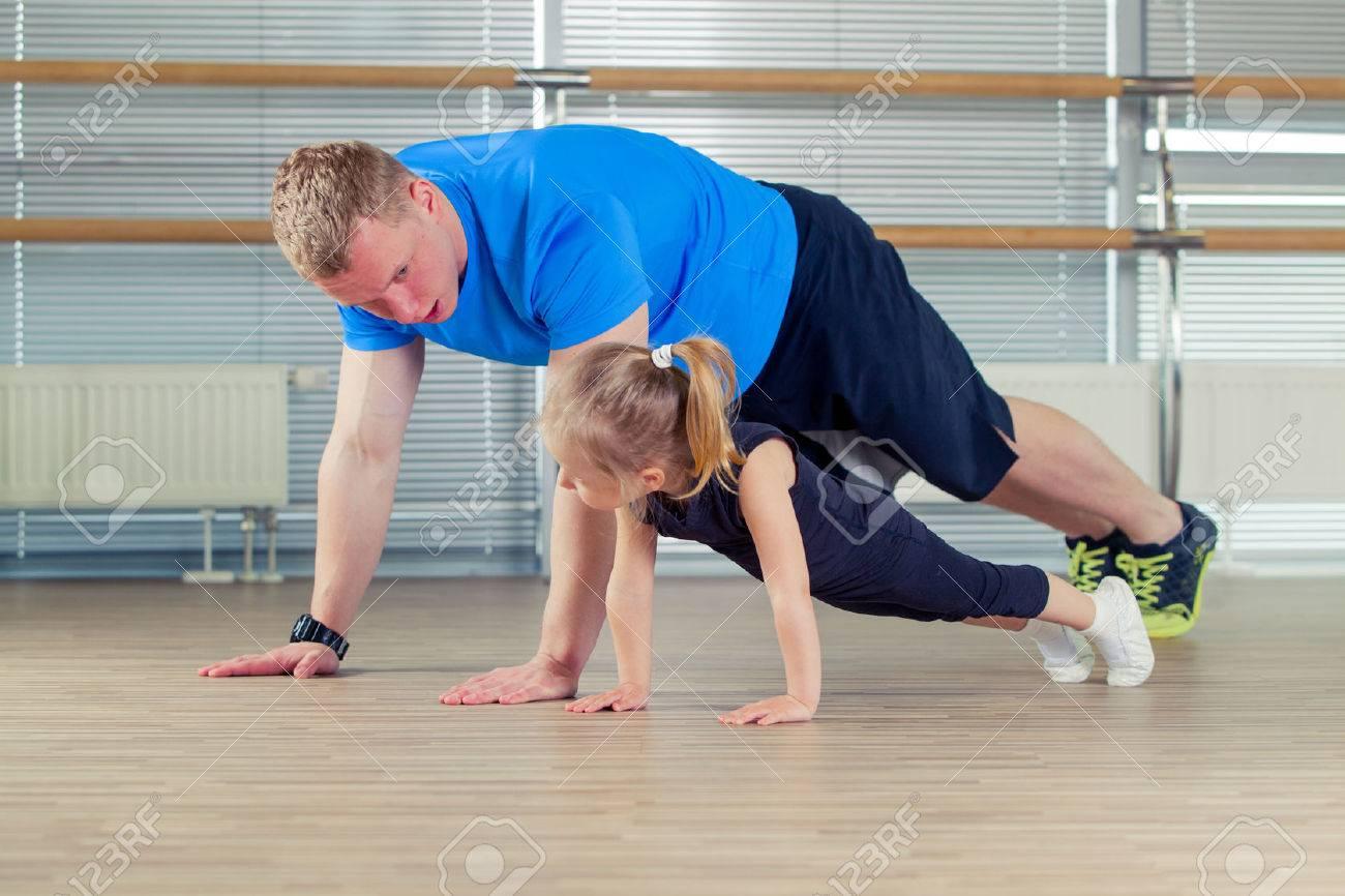 Group of children doing kids gymnastics in gym with nursery teacher. - 58397253