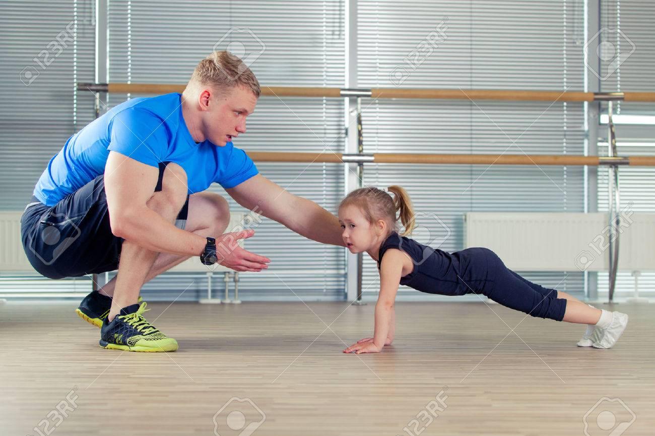 Group of children doing kids gymnastics in gym with nursery teacher. - 58398247