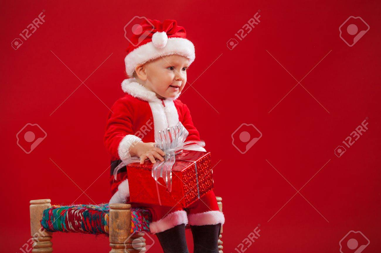 Beautiful little baby celebrates Christmas. New Year's holidays. Baby in a Christmas costume with gift - 65291291