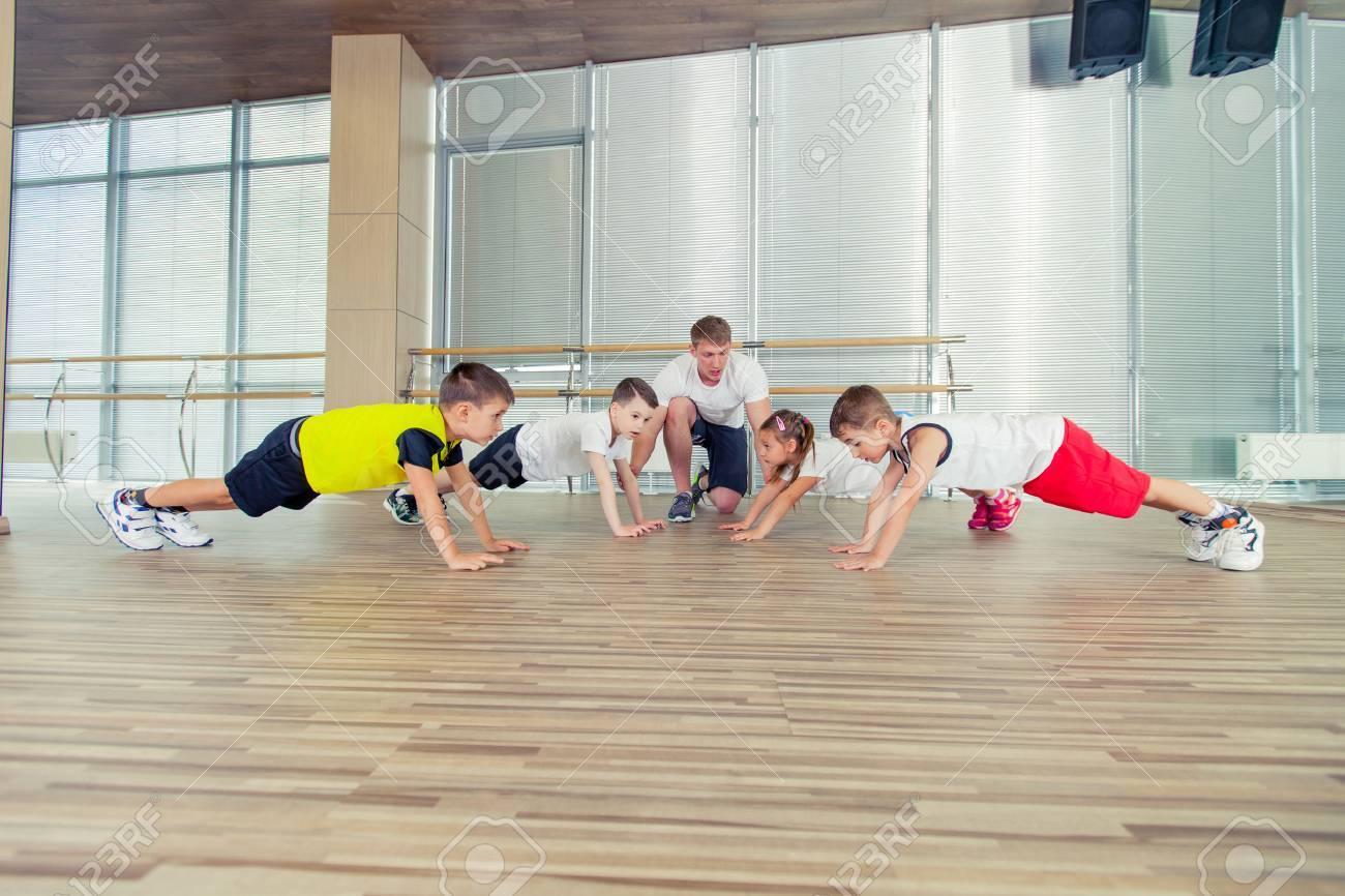 Group of children doing kids gymnastics in gym with nursery teacher. - 65293813