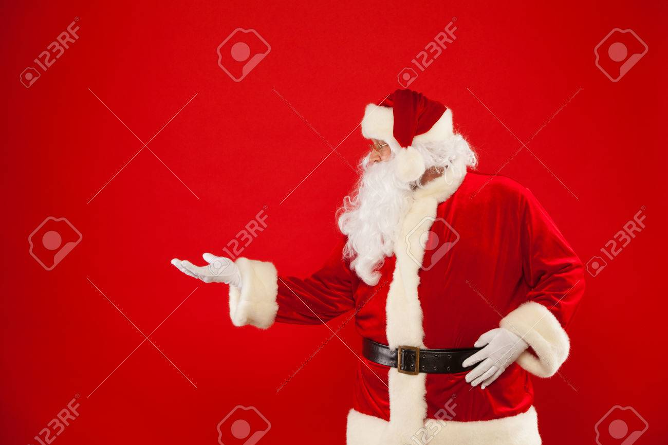Santa Claus pointing in blank a place, red background. Merry Christmas - 65294721