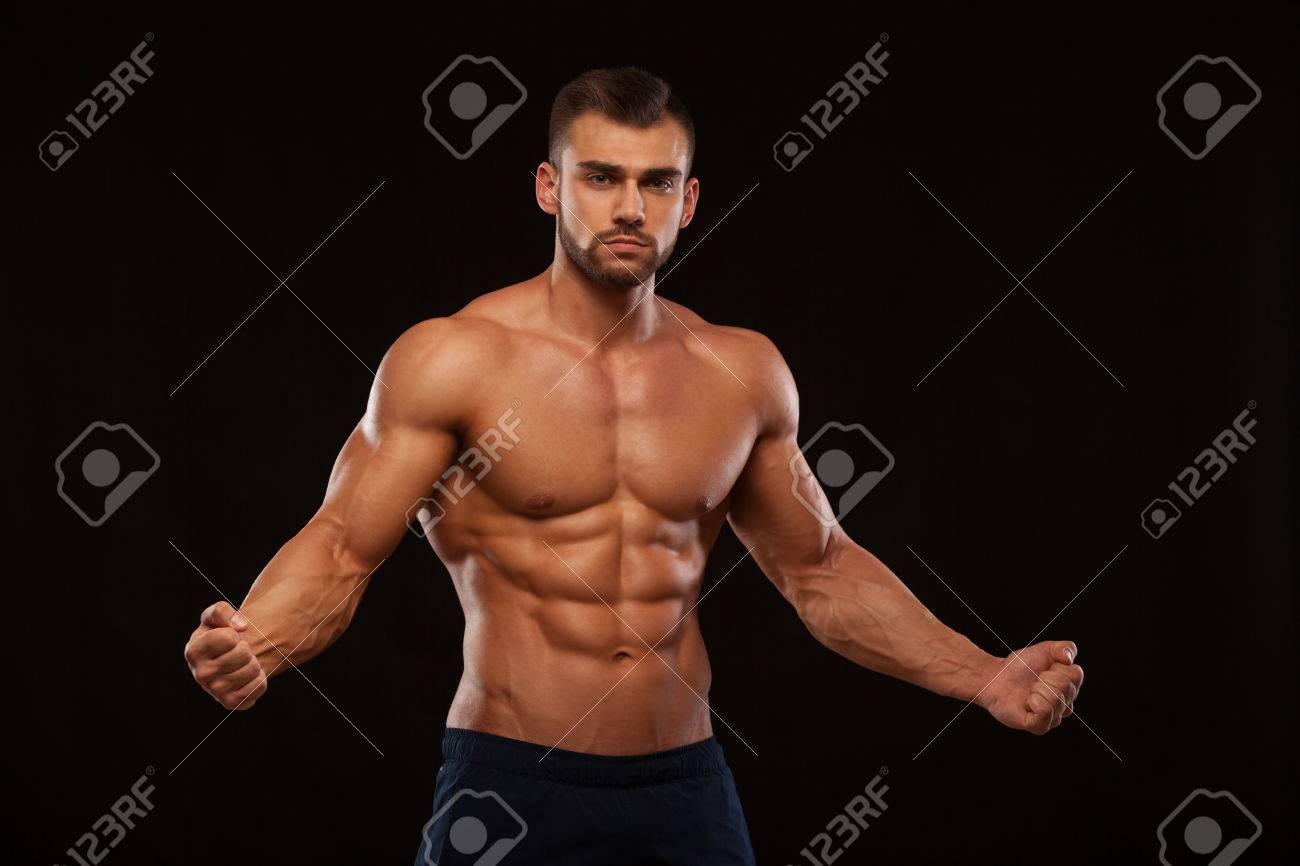 Strong Athletic Man Fitness Model Torso showing six pack abs. isolated on black background with copyspace - 76349279