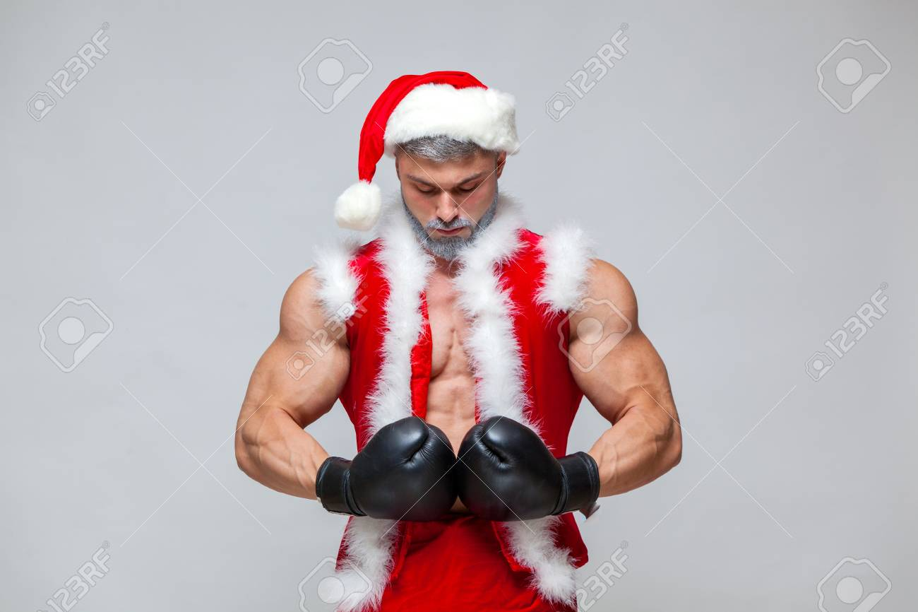 06116f8b7d80d Sexy Santa Claus with boxing glove. Young muscular man wearing Santa