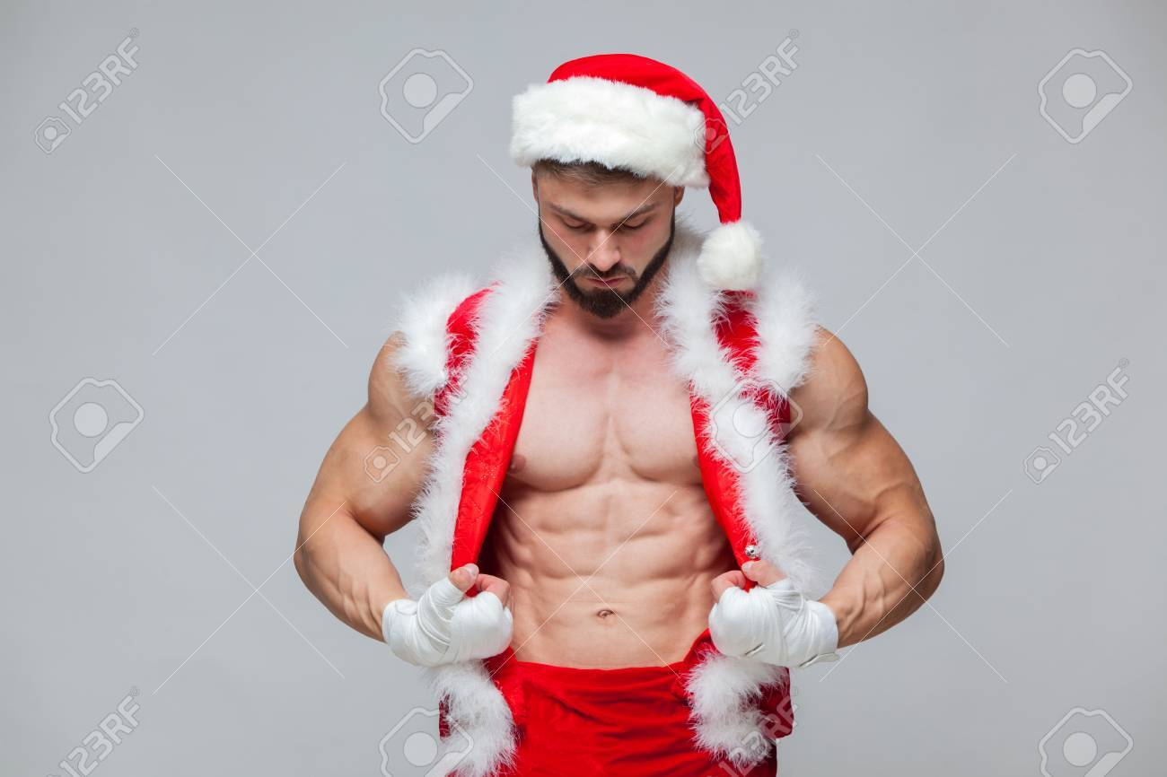 90f88fdd6b184 Christmas. Sexy Santa Claus . Young muscular man wearing Santa Claus hat  demonstrate his muscles