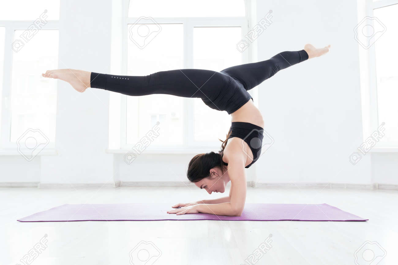 Young woman practicing yoga, standing in handstand exercise, working out, wearing black sportswear, on the floor near window - 145546840