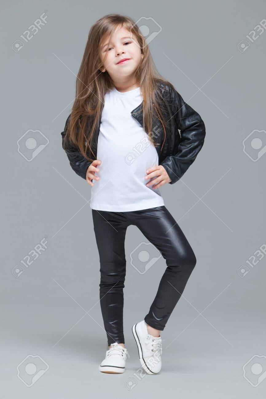 Baby girl with long hair in black leather jacket and leggings is standing in the studio on grey background - 146032160