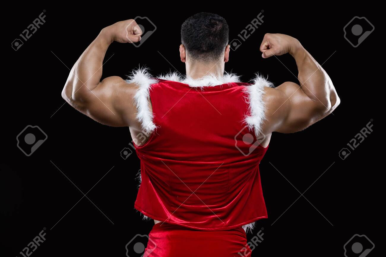 Back view of young Santa Claus showing off his strong biceps isolated on black background - 157778095