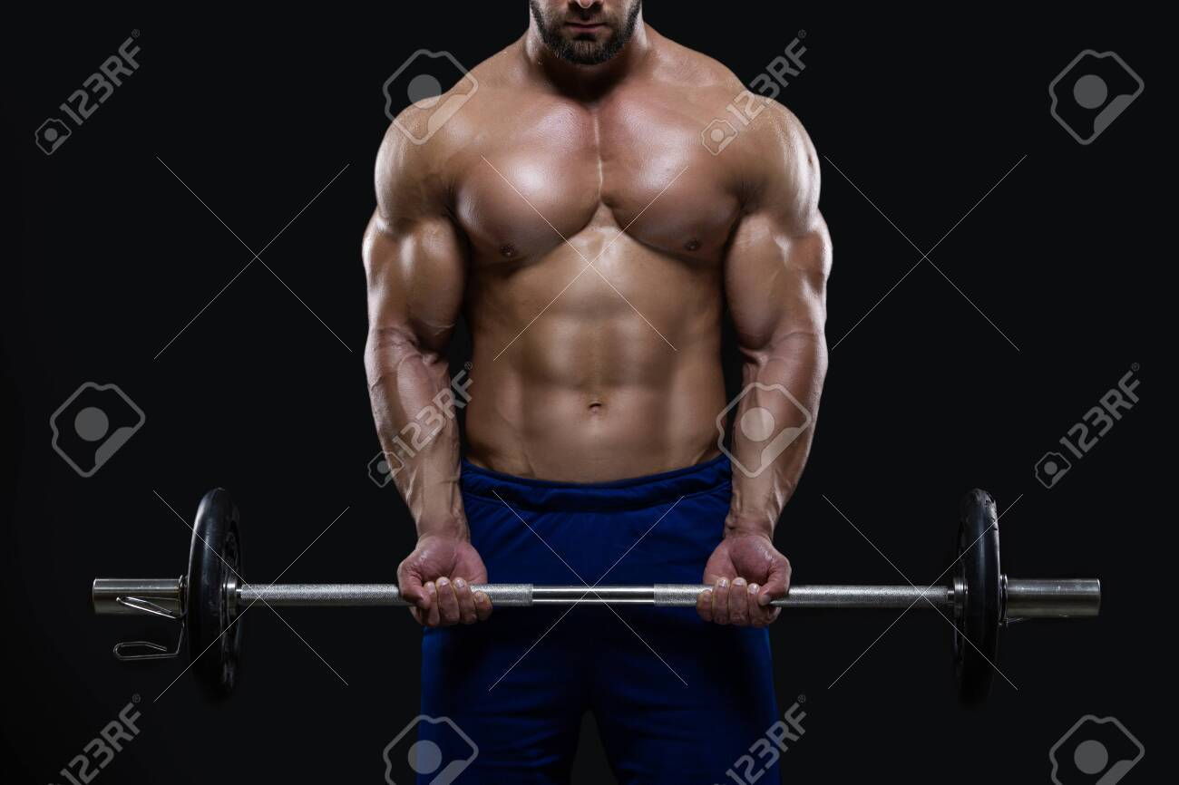Handsome fitness man is standing with a heavy barbell ready to workout isolated on black background - 158188785