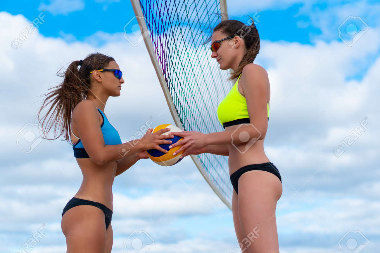 A girl in a yellow bathing suit passes a volleyball into the hands of a girl in a blue bathing suit on the beach - 158341516