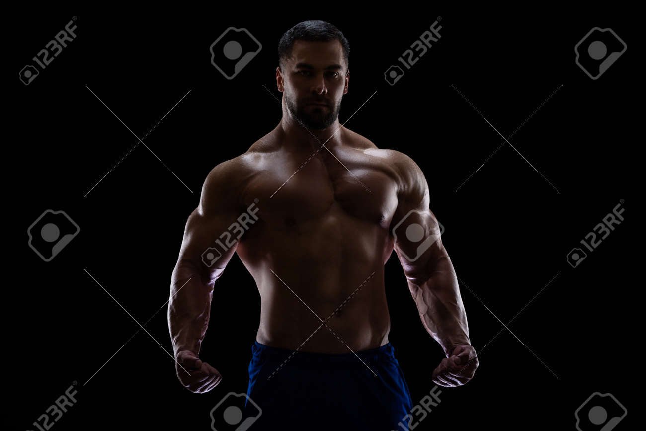 Portrait of a bodybuilder standing isolated on black background in a shadow with clenched fists to show off his muscles - 165407068