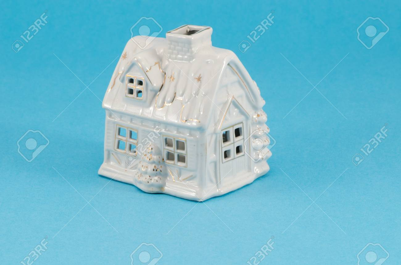 Small White Ceramic Toy Christmas House Decoration On Blue