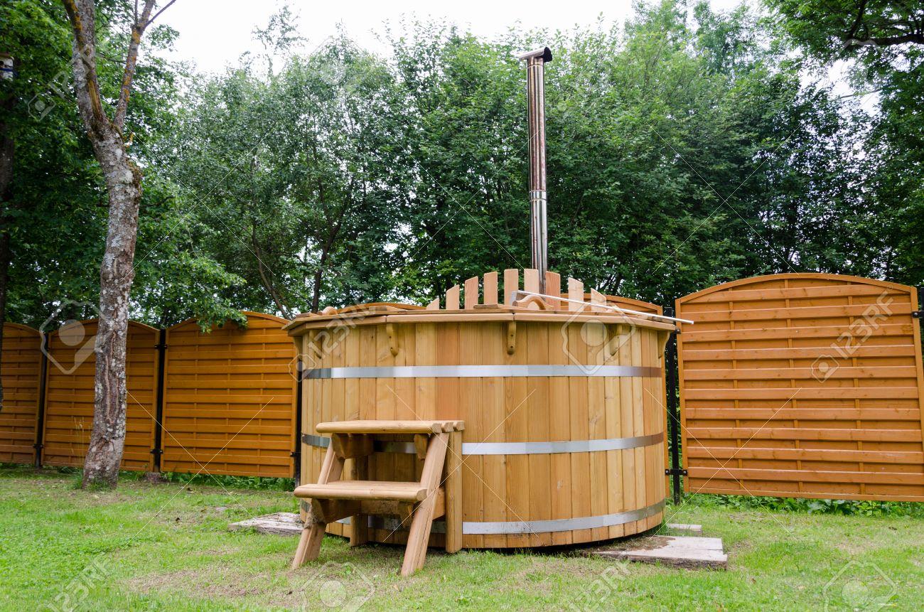 Bois spa d\'eau bain à remous rustique avec des escaliers dans le jardin cour