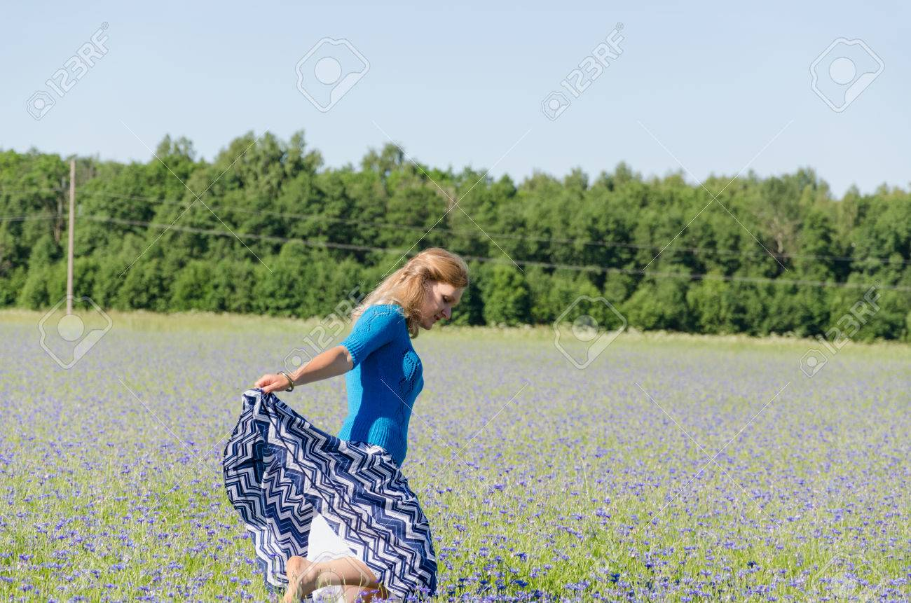 young girl dance in the endless cornflower meadow summer time Stock Photo - 28911284