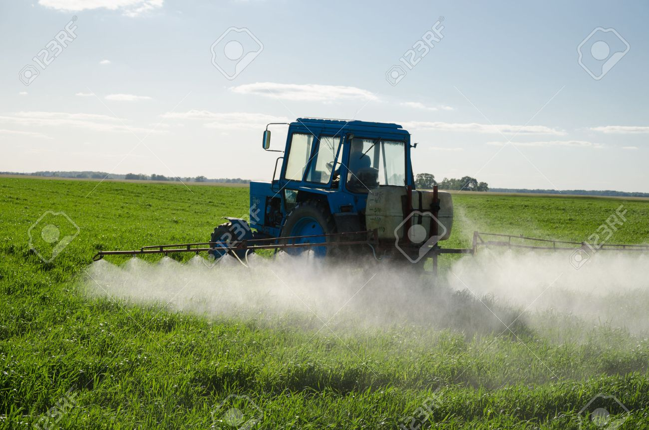 Tractor spray fertilize field with insecticide herbicide chemicals