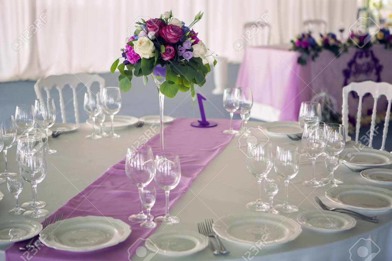 休日、結婚式、誕生日パーティーの装飾の設計中央、白いテーブル クロス、ワイングラス、ガラス スタンド花瓶の花、バラ、葉のついた枝でラウンド  テーブル紫ライラック ストライプ