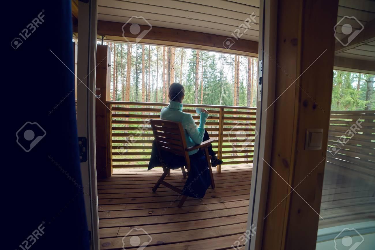 Niña En Un Suéter Azul Sentado En Una Silla De Madera Y Beber Té De Una Taza Blanca En La Terraza Del Segundo Piso Balcón En La Casa En El Bosque De