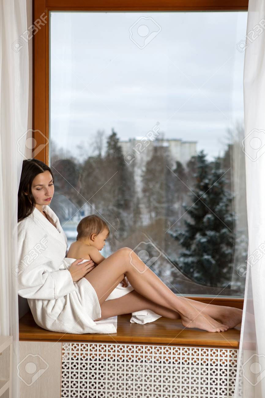 Mom With Little Son Sits On The Window In A Bathrobe After A Shower Stock Photo